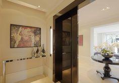 Hall social bastante imponente com portas em laca brilhante preta, aparador espelhado e quadro com retalhos de papel.