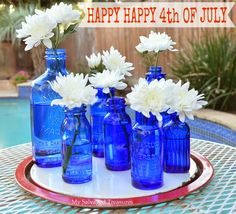 4th of July display of cobalt blue bottles with white blooms served up on a red and white tray. From MySalvagedTreasures.com