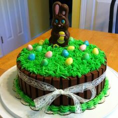 How cute! Just bake 2 - 9 inch round cakes, frost, line with kit kats and a ribbon, pipe the grass on and add the bunny and eggs!