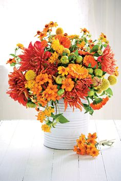 Much like a Southern girl can stay fresh-faced despite the heat (nose powdering should be considered a regional art form), these fiery blooms stand up to our August scorchers. For this display, we snipped dahlia and dahlia buds, lantana, and zinnia to form a loose cluster. Yellow Billy buttons and calendula from a local florist round out the mix. Bonus: Including yet-to-bloom buds ensures an arrangement with staying power.