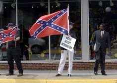 Walter Ring, who stands in the center holding a Confederate flag, drove from the Richmond area to protest the Faith and Politics Institute's delegation to observe how residents of Farmville, Virginia are dealing with racial integration. He catches the attention of A. P. Jackson, a local lawyer. Prince Edward county closed its public schools from 1959 to 1964 instead on integrating them, April 30, 2006. Photo credit: Chris Maddaloni