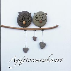 """2 owls with hanging love hearts"" #agifttorememberart #pebbleart #nature #etsy #makersgonnamake #giftideas #giftshop #owl #love #handmadewithlove #instaphoto #instaart #instagood #recycledart #cute #frame #art #interiordesign #anniversary #engagement #stones"