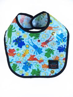 """Baby Bib in """"FROGGIES"""" Patten. We invite you to splatter and slop all over the place with IMPWEARhome bibs. A growing toddler most likely means that they are the messiest in the family! Keep them clean of pudding, and the floor clean of cheerios. Measures 9""""w x 12""""h, has a crumb catcher pocket and easy-snap closure. WIPE 'N' WASH: 100% Cotton, Laminated; Splash, Slop, Spill Proof; Durable & Long-Lasting. Water-based urethane laminated cotton CPSIA certified, BPA & Phthalate-free…"""