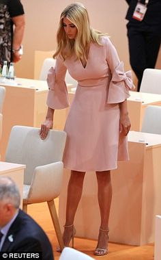 Ivanka Trump takes her seat at the beginning of the third working session of the G20 meeting. Pale pink blush dress with bow detail on sleeves, high heels. July 2017