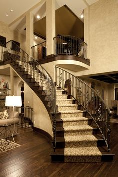 I love the curved staircase with the carpet up the dark wood steps. Good contrast and addition to break up all the wood.