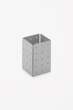 This compact pen holder is made from perforated metal with a powder coating. Its simple shape is designed to combine easily with other storage to ensure a tidy desk.