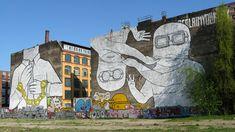"""Die beiden Graffiti des italienischen Street-Art-Künstlers Blu entstanden in den Jahren 2007/2008 und erstreckten sich über die fensterlosen Seitenfassaden von zwei Häuserblocks, die an die Brache angrenzen. Das erste Bild kreierte Blu im Sommer 2007 im Rahmen des """"Planet Prozess"""", einem Ausstellungsprojekt des Berliner Kunstvereins Artitude zur Street-Art."""
