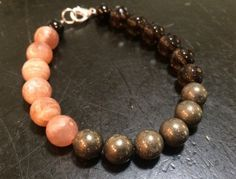 Positive Energy Bracelet Made with Sunstone, Smoky Quartz, Black Tourmaline, and Pyrite Metaphysical Properties: Sunstone: With the radiance of the sun and the fire of the solar ray, Sunstone carries