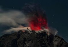 In this timed-exposure night photo taken early on February 12, 2017, Mount Sinabung volcano spews reddish clouds of ash, as seen from the Karo district in North Sumatra province. Activity levels have increased in the past week, with Sinabung shooting hot ash clouds into the sky dozens of times, according to the local volcano monitoring agency.