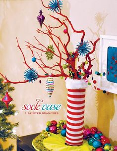 Sock Vase Centerpiece ~ take cute holiday socks (dollar store) cut the toes off and slide onto vase