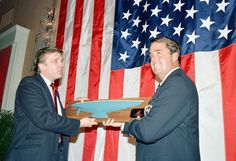"""Dennis Conner, right, skipper of """"Stars and Stripes,"""" receives a model depicting the hull of his winning yacht from real estate developer Donald Trump during a reception for Conner and his crew in New York City, Feb. 10, 1987. Trump was one of the many financial backers for Conner's America's Cup challenge and paid for a New York parade for the winners."""