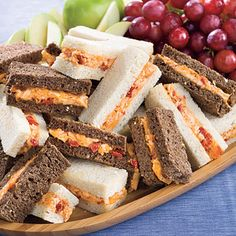 "Smoky ""Pimiento"" Cheese Sandwiches  Smoked Cheddar and Gouda cheeses and sun-dried tomatoes provide a terrific twist on traditional pimiento. Spread on sourdough and dark wheat bread and cut into smaller sandwiches for easy pickup. Serve with grapes and apples."