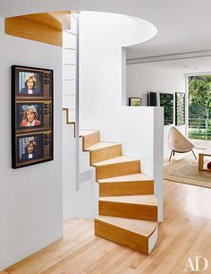 A piece by Robert Heinecken hangs next to the spiral staircase | archdigest.com