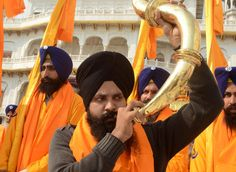An Indian Sikh devotee plays a musical instrument as he walks with Punj Pyara holding flags of the Sikh religion as they escort a procession from Sri Akal Takhat at The Golden Temple in Amritsar on Nov. 23, 2012, on the eve of the Martyrdom Anniversary of the Ninth Guru of Sikhism, Sri Guru Teg Bahadur. Sri Guru Tegh Bahadur Sahib was born at Amritsar in 1621 and was the youngest son of Sri Guru Hargobind Sahib. (Photo credit: NARINDER NANU/AFP/Getty Images)