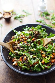 Roasted Sweet Potato, Wild Rice, and Arugula Salad in a bowl with wooden spoons.