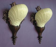 Bronze, Bulbous, Bold, and Old.  A marriage of Art Deco and Rococo styles created this wonderful pair of late '20s to early '30s vintage wall sconce light fixtures. They were made with the best materials of the day for a production item, bronze and custard glass. The patina has taken on a deep amber hue; the custard glass slip shades are in near mint condition…