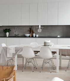 Kitchen: matt white handleless cabinets, grey stone splashback, black stone benchtop, chrome mixer tap, white extendable dining table, white Eames Eiffel chairs, pale floorboards, exposed lightbulb pendant light with white cord, plant in white vase