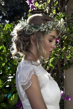 Beach wedding hairstyle idea: A soft and romantic updo with a greenery/floral crown. Perfect for a destination wedding or wedding at the beach.
