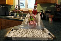 Elf on the Shelf 2010 (Fizzy): 12.11: She woke up to find Fizzy was stuck to the slide and so were the slide's big marshmallows. She moved Tink up to the slide and helped herself to some of the big ones lining the jelly roll pan. I think it is funny how symmetrical the ones she left were.