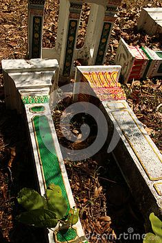 Buddist and animist Asian spirit houses: Perspective 2-shot view of Pedestals used to support local spirit houses in Southeast Asia, lying in a field among dry leaves near a holy site.