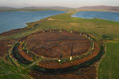 The Ring of Brodgar (alternative spelling Brogar) comprises a massive ceremonial enclosure and stone circle probably dating from between 2500 and 2000 BC. Around it are at least 13 prehistoric burial mounds and a stone setting (2500-1500 BC).( Scotland ) (Kite Photography )