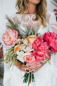 This bride went for bold and beautiful with her luscious wedding bouquet. A vibrant bouquet of pink, yellow, and orange peonies and roses. This bouquet was perfect for the brides tasseled, embroidered, and sheer wedding dress. A bridal look for a vintage or even boho wedding in the summer. Click for more beautiful peony bouquets. // Photo: Fig Tree Pictures
