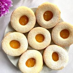 7 linzer cookies with reduced-ugar apricot jam on a white plate