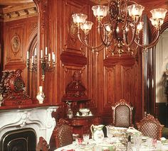 """Dining Room looking southwest. The chestnut paneled walls, marble mantel, furnishings, and gas fixtures are all original to the room. The French porcelain, cut glass stemware, and Tiffany-retailed silver were ordered by the Morses when the house was built."""