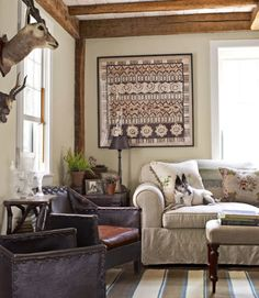 This living room in this Rhode Island home relies on much of the building's original elements, such as the restored windows and glass shown. The furnishings and accents include forties French leather armchairs, a framed batik print from Bali, and a flat-weave Peruvian rug. Mixed in among heirloom items are practical, comfortable additions, like deep-upholstered seating and no-fuss cotton fabrics.