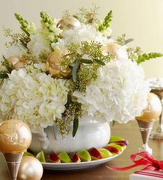 un arrangement de fleurs blanches et boules de Noël de couleur or