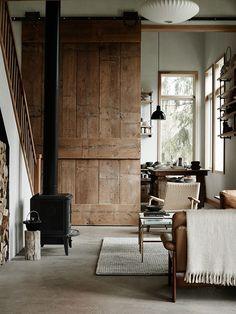 Salón rural. Estufa, escalera, puerta corredera de madera aserrada, muebles vintage, hormigón pulido.