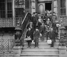 Charity: A group of men and young boys stand outside the front entrance of the Children's Aid Society's central office, at 24 St. Mark's Place, circa 1895. The children hold satchels with their belongings. They children were preparing to travel west, subsidized by Mrs John Jacob Astor