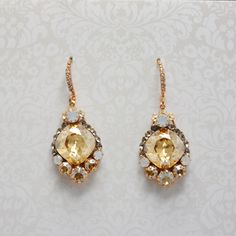 golden shadow cushion cut swarovski chandelier, set in a rose gold finish. rose gold pave french hook. accented with greige and white opal swarovski. designed by haute bride