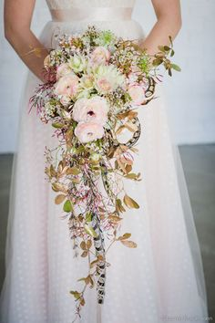 Green Goddess Flower Studio, cascading bridal bouquet of ranuncs, wax flower, blushing bride, andromeda, gold foliage, and feathers