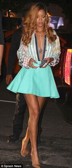 Rihannas plunging shirt revealed the intricate tattoo across her ribcage