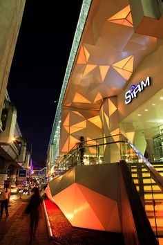 The illuminated exterior of the Siam Center shopping mall, located on Thanon Rama 1 road in the Pathum Wan district of Bangkok.