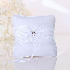 Ce petit coussin avec dentelle sera le porte alliances idéal pour une cérémonie chic et sobre. Deux rubans de satin blanc vous permettrons de nouer les alliances. Le petit coussin porte alliance possède deux petite fleurs.