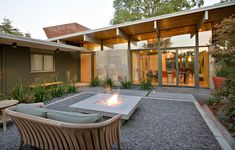 Arts and crafts built ins patio midcentury with decorative pebbles overhanging eaves concrete paver path