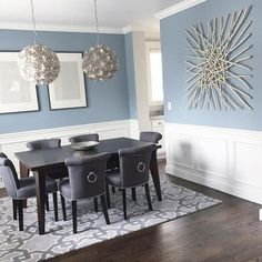 modern coastal dining area with wainscoting walls that highlight the blue color