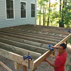 A man using an impact driver to attach a rim joist to a deck frame. Building A Deck Frame, Deck Building Plans, Building A Porch, Build A Deck, Wood Deck Plans, Floating Deck Plans, Freestanding Deck, Deck Framing, Deck Steps