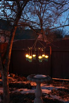 outdoor chandelier made with old insulators and an old garden fence.
