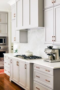 A gray wood paneled kitchen vent hood stands over a white marble herringbone backsplash and an integrated gas cooktop.