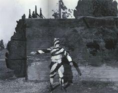 """""""Tromper l'ennemi – L'invention du camouflage moderne en 1914-1918"""" de Cécile Coutin. Un observateur américain en tenue camouflée noire et blanche qui pose au revers d'une paroi de bois représentant, à l'avers, une haie factice. Sa tenue bariolée lui permet de se confondre avec les branches des arbres dans lesquels il monte pour observer l'ennemi."""