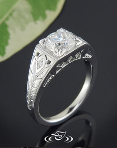 Custom platinum antique styled engagement mounting to hold floral 4-prong set diamond. Beautiful bead set brilliant cut melee diamonds and pierced square design on top face with wheat engraving down shoulders. - See more at: