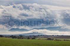 Stock image of 'Early afternoon scenery of cereals fields and little town with castle between the fog, Nogales, Spain'