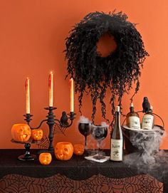 Several decor elements I like: black mossy wreath, matte black candelabra, drippy candles, black glassware and vintage-looking labels