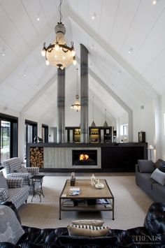 The large family living area beyond the formal entry to this large country house is open to courtyards on two sides.  The raked ceiling and beams are painted white to enhance the fresh, airy look of the living room. The house was designed by Lat Forty Five.