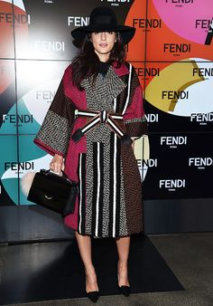 Eleanora Carisi wearing a wide brimmed hat and a belted statement coat at MFW