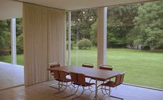 A midcentury dining room designed by Mies van der Rohe with exposed structure, walls of glass, a curtain partition and simple dining set.