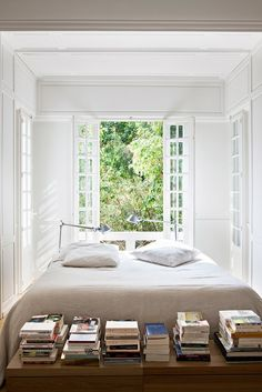 A bright and airy bedroom with stacked books on the bed end.